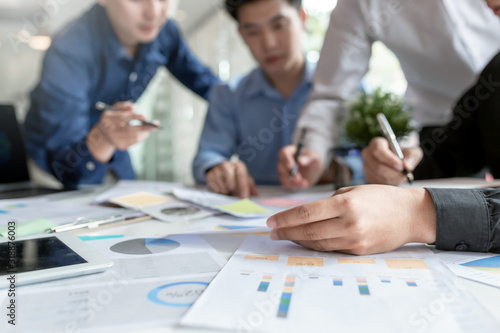 Fototapeta New generation group of asia businessman in smart casual wear together to analyze the financial data graph at work. obraz