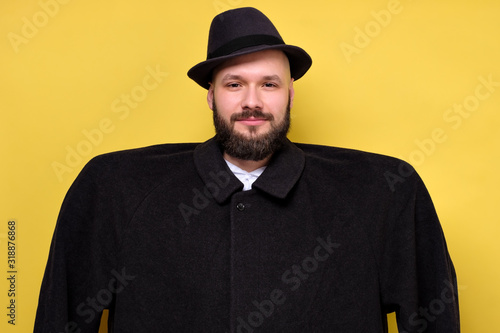 Man in oversize baggy black coat and hat smiling standing on yellow studio Canvas Print