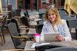 Woman Using Digital Tablet While Sitting At Sidewalk Cafe In City