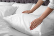 Woman fluffing soft pillow in bedroom, closeup