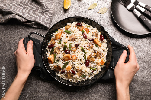 Woman with delicious rice pilaf at grey table, top view Wallpaper Mural