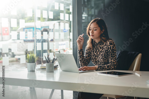 Young asian businesswoman sitting on her workplace in the office. Young woman working at laptop in the office.