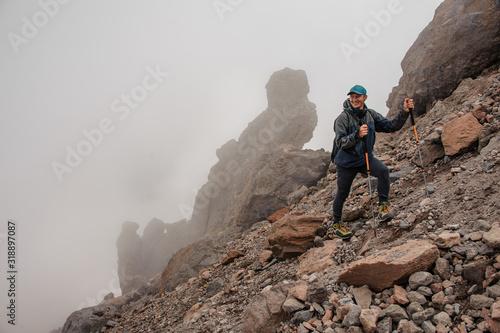 Fototapeta Smiling trekker stands on a mountain side obraz