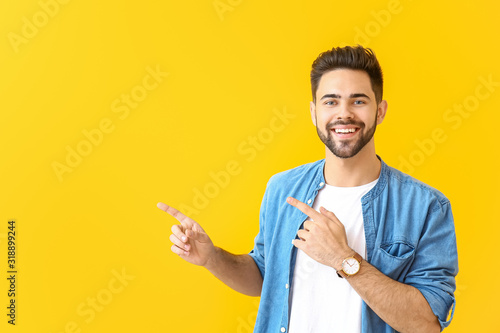 Obraz Handsome young man pointing at something on color background - fototapety do salonu