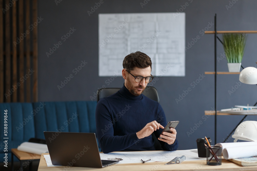 Fototapeta Young man using smartphone and smiling. Happy businessman using mobile phone apps, texting message, browsing internet, looking at smartphone. Concept of young people working with mobile devices.