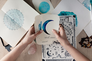 Top view of astrologer holding watercolor paintings with moon phases on cards by birth chart on table