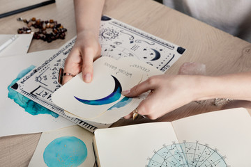 Cropped view of astrologer holding cards with watercolor drawings by birth chart with zodiac sign on table