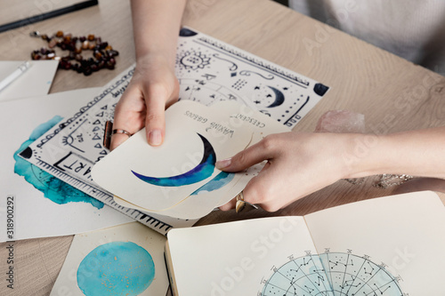 Cropped view of astrologer holding cards with watercolor drawings by birth chart Canvas Print