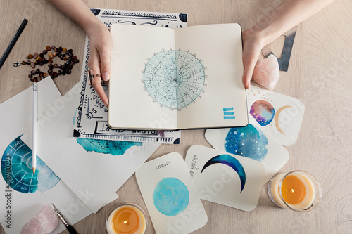 Fotografie, Obraz Top view of astrologer holding notebook with watercolor drawings and zodiac sign