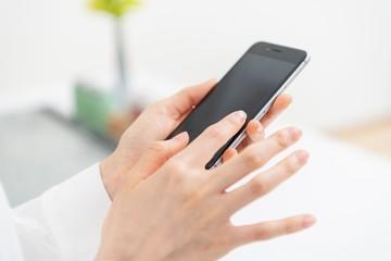 スマートフォンを操作する女性の手元