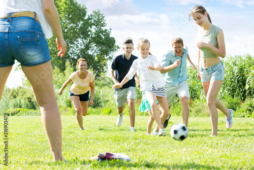 Fototapeta Parents with children playing football on outdoor obraz
