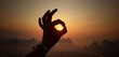 Cropped Hand Gesturing Ok Sign Against Orange Sky During Sunset