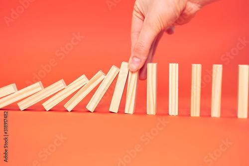 Fototapeta hand finger stops falling wooden dominoes, red background, domino principle, business concept obraz na płótnie