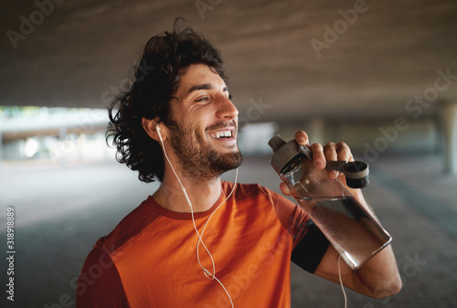 Fotografie, Obraz Portrait of a smiling cheerful young man with earphones drinking water from reus