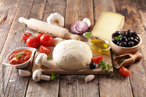 Fototapeta raw dough pizza with oil, tomato, olive, mushroom and cheese obraz