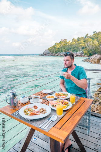 Young Man Sitting At Table By Sea Against Sky - fototapety na wymiar