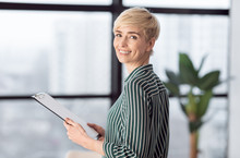 Successful Businesswoman Holding Folder Standing In Modern Office