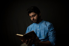 Fashion Portrait Of Young Indian Bengali Brunette Man With Traditional Cotton Wear Holding Pencil And Book In Black Copy Space Background. Indian Lifestyle And Fashion