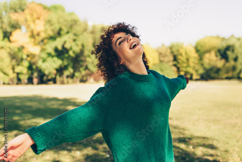 Horizontal image of happy young woman smiling posing against nature background with windy curly hair, have positive expression, wearing in green sweater Fototapete