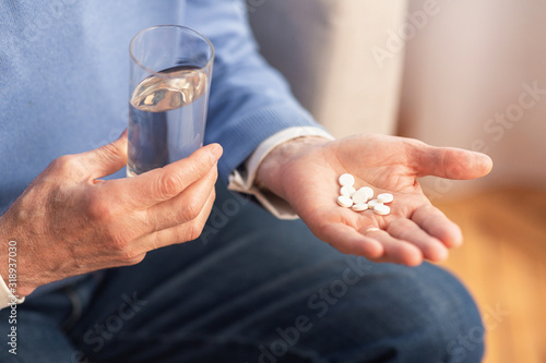 Unrecognizable Gentleman Holding Pills Sitting On Sofa At Home, Cropped