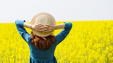 Girl Walking In A Field Of Yel...