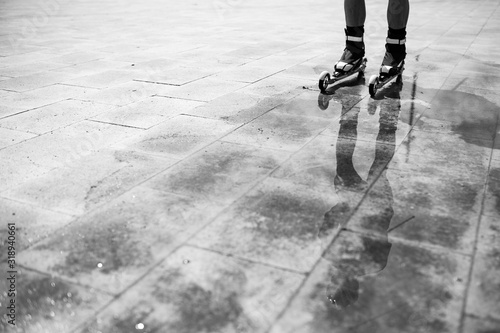 Obraz Low Section Of Person Inline Skating On Wet Tiled Floor - fototapety do salonu