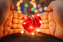 Holding A Red Heart Shape Covered With Led Lights On Wooden And Bokeh Lights Background. Valentines Day And Romance Concept.