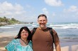 Leinwandbild Motiv Portrait Of Smiling Overweight Couple Standing At Beach Against Sky
