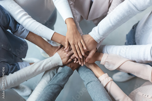 Multiracial business team putting hands on top of each other