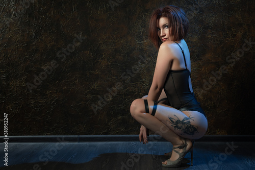 Sexy red-haired young woman in a bdsm costume