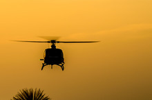 Low Angle View Of Silhouette Helicopter Against Sky During Sunset