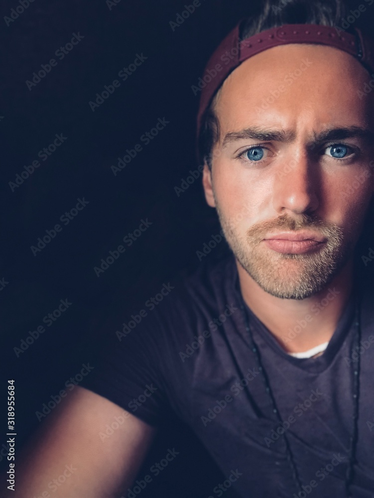 Fototapeta Close-Up Portrait Of Young Man Over Black Background