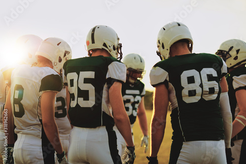 Fototapeta American football players standing in a huddle before a game obraz