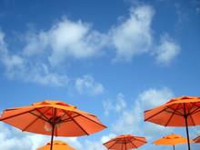 Low Angle View Of Orange Beach Umbrellas Against Sky