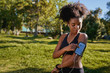 Close-up of an african american female runner athlete listening to music from smart phone in armband - young active black woman