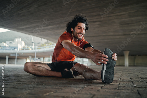 Smiling portrait of a fit young man sitting under the concrete bridge stretching his legs before running
