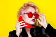 canvas print picture - Portrait of a glamorous blonde in a fur coat with a red banana and sunglasses. The blonde is talking on a banana on a yellow background.