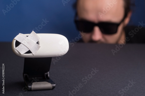 Fotografia in the foreground a webcam sealed with adhesive tape, in the background a man in black glasses is watching a caller on another line