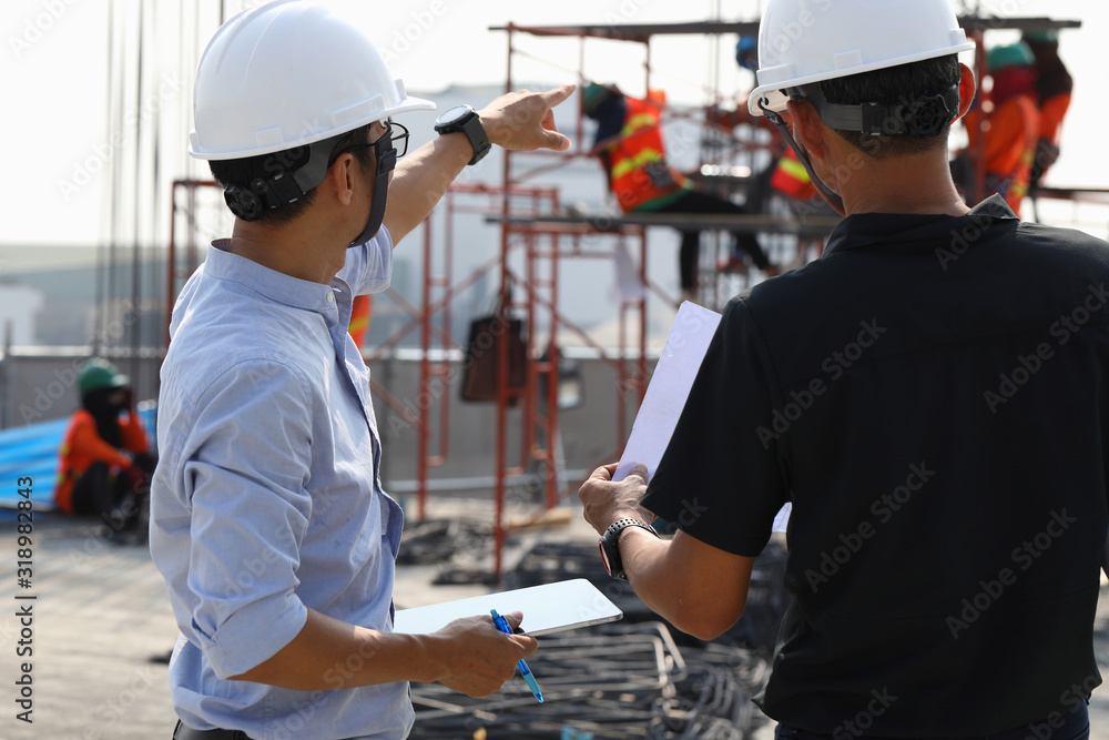 Fototapeta Two engineers work on the construction site. They are checking the progress of the work.