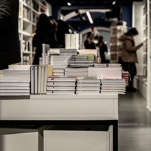 Stacks Of Books On Table, Modern Urban Bookshop, Library. Unrecognizable Silhouettes Of People. Education Concept, Reading Fiction, Knowledge, Life Style