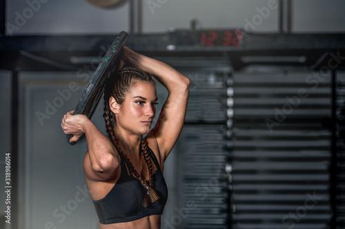 Young sweaty muscular strong fit girl holding big heavy barbell weight plate wit Tapéta, Fotótapéta