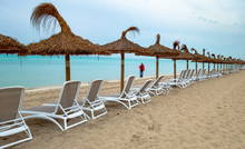 Man Standing By Lounge Chairs And Thatched Roof At Beach