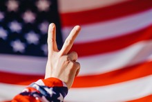 Cropped Hand Gesturing Peace Sign Against American Flag
