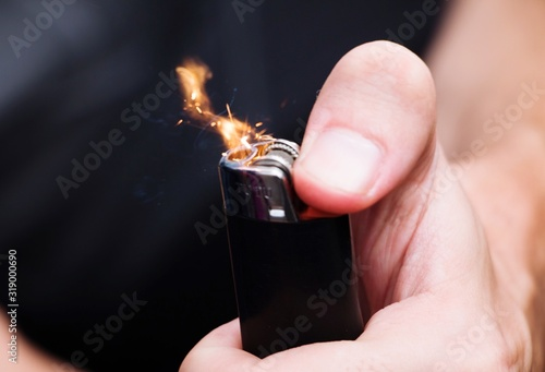 Photo Midsection Of Person Igniting Cigarette Lighter