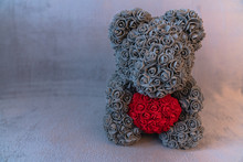 Close Up Photo Of The Grey Teddy Bear That Sitting On Sofa And Holding Red Heart
