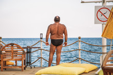 Adult Hairy Man Standing At Sea Beach Sunbathing Looking At Beautiful Blue Sea Water. Horizontal Color Photography.