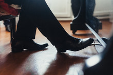 A Male Musician Plays The Piano, Presses The Foot In Black Shoes On The Pedal Close-up. Photography, Concept.