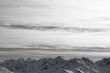 Leinwanddruck Bild Snowy high mountains and sunlit cloudy sky at winter evening