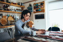 Young Man Holding His Dog In Nap While Using Laptop In Kitchen