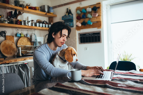 young man holding his dog in nap while using laptop in kitchen Canvas Print